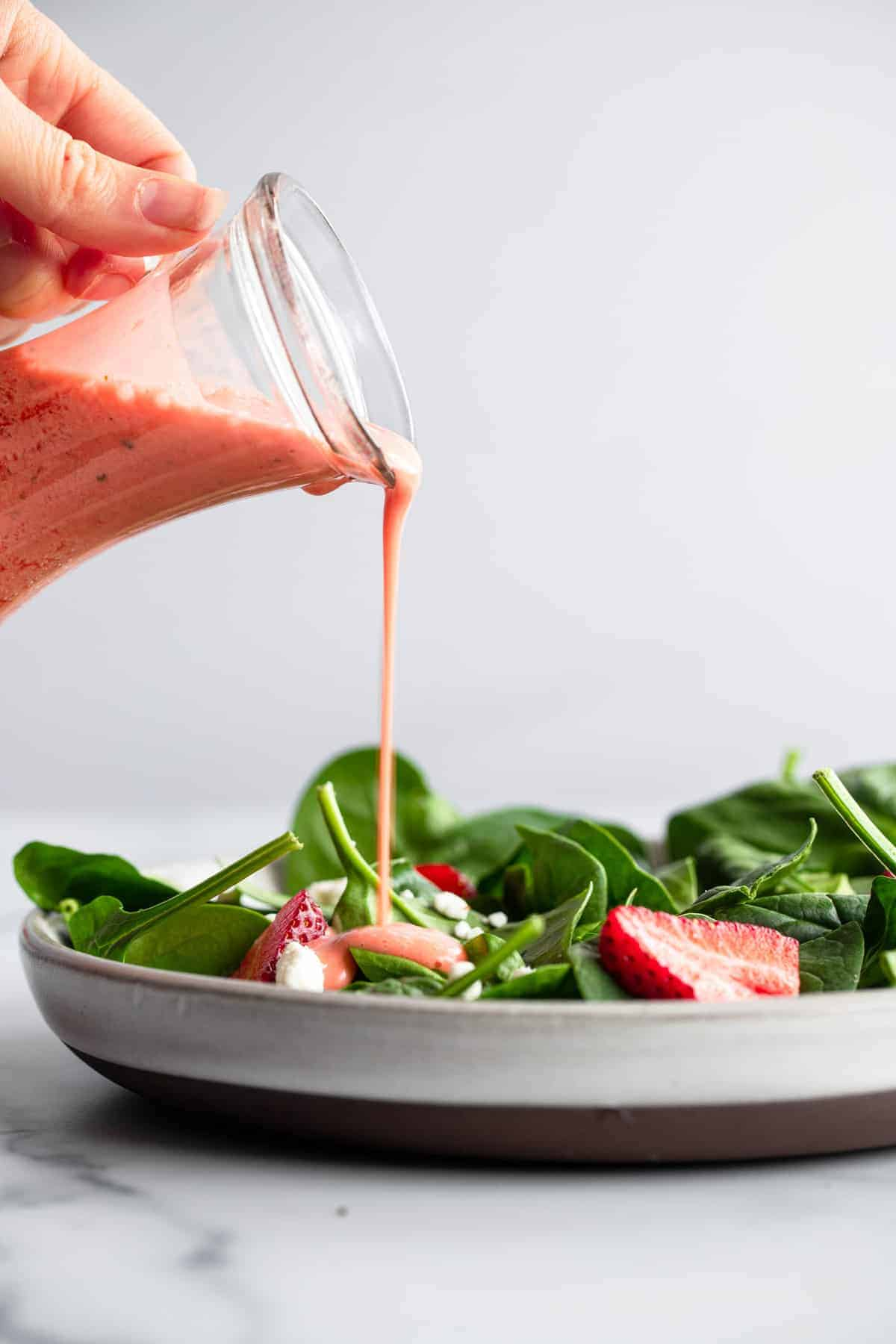 strawberry salad dressing being poured over a salad on a plate