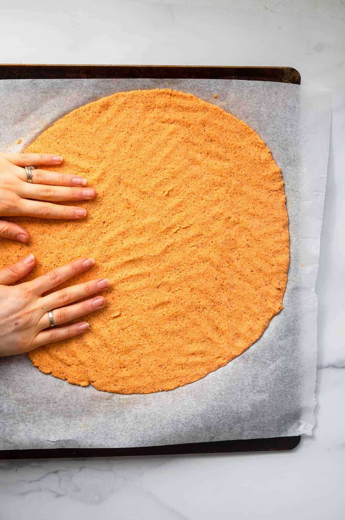 Sweet Potato Crust being pressed on to a baking sheet