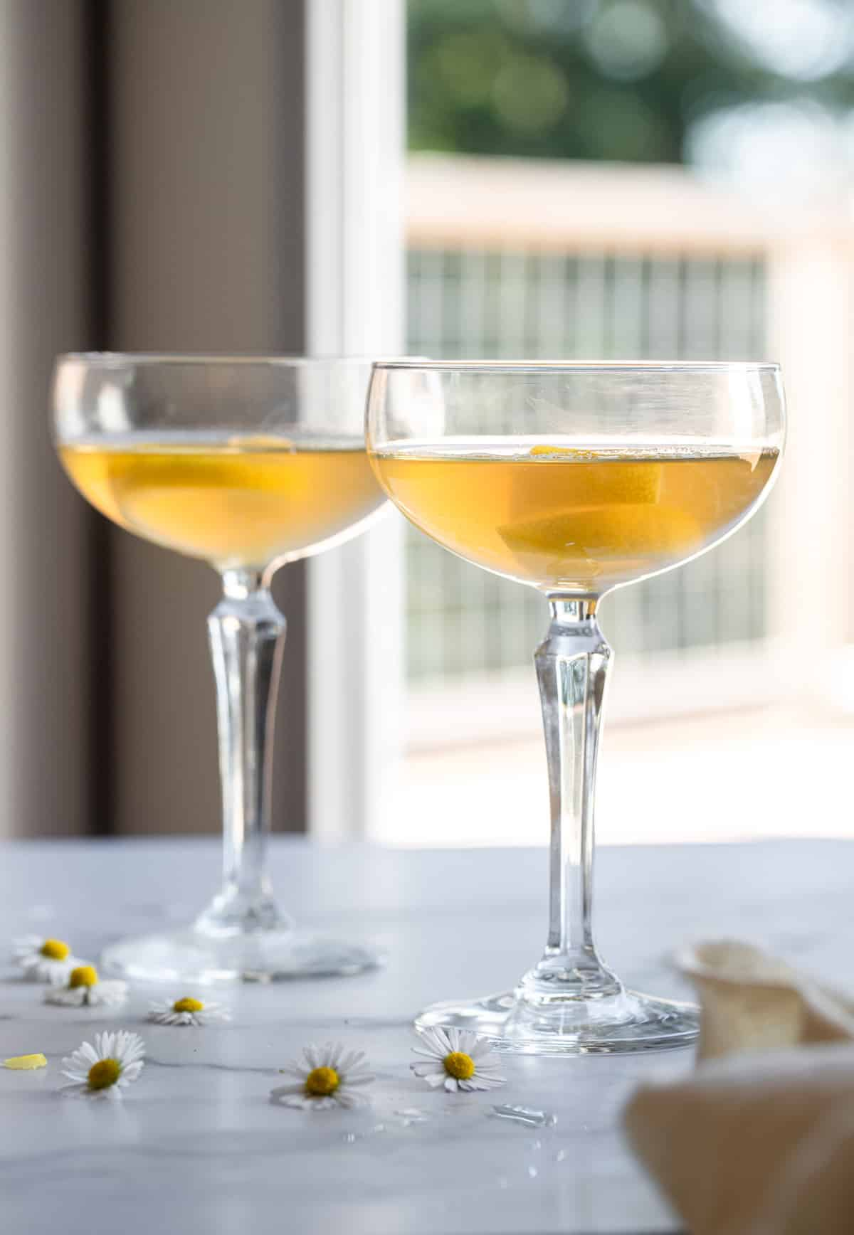 two bees knees cocktails on a table in cocktail glasses