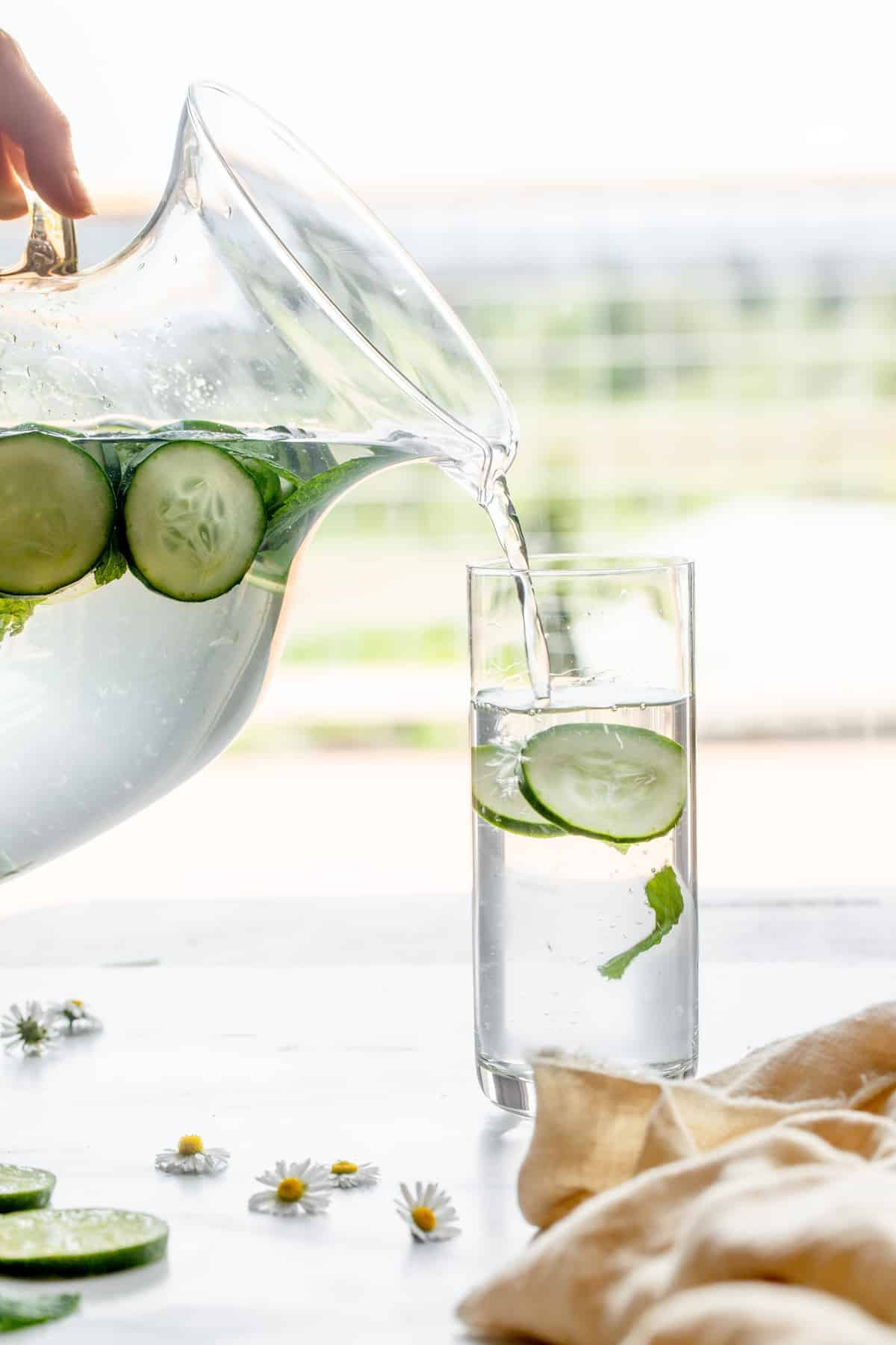 cucumber mint water being poured into a skinny serving glass