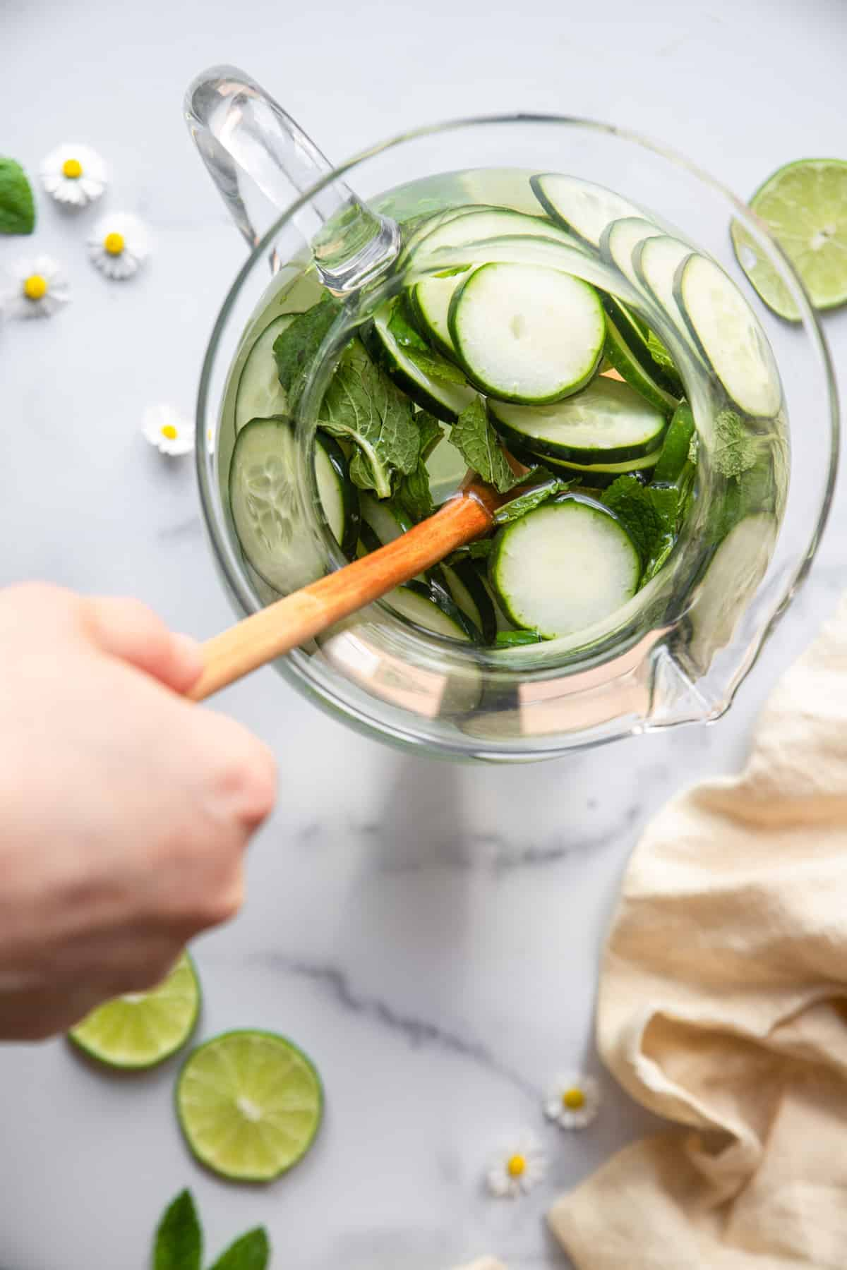 top view of cucumber mint water being stirred with a wooden spoon
