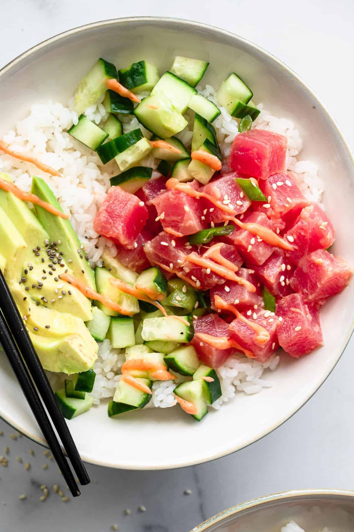 Tuna poke bowl close up in serving bowl with chopsticks