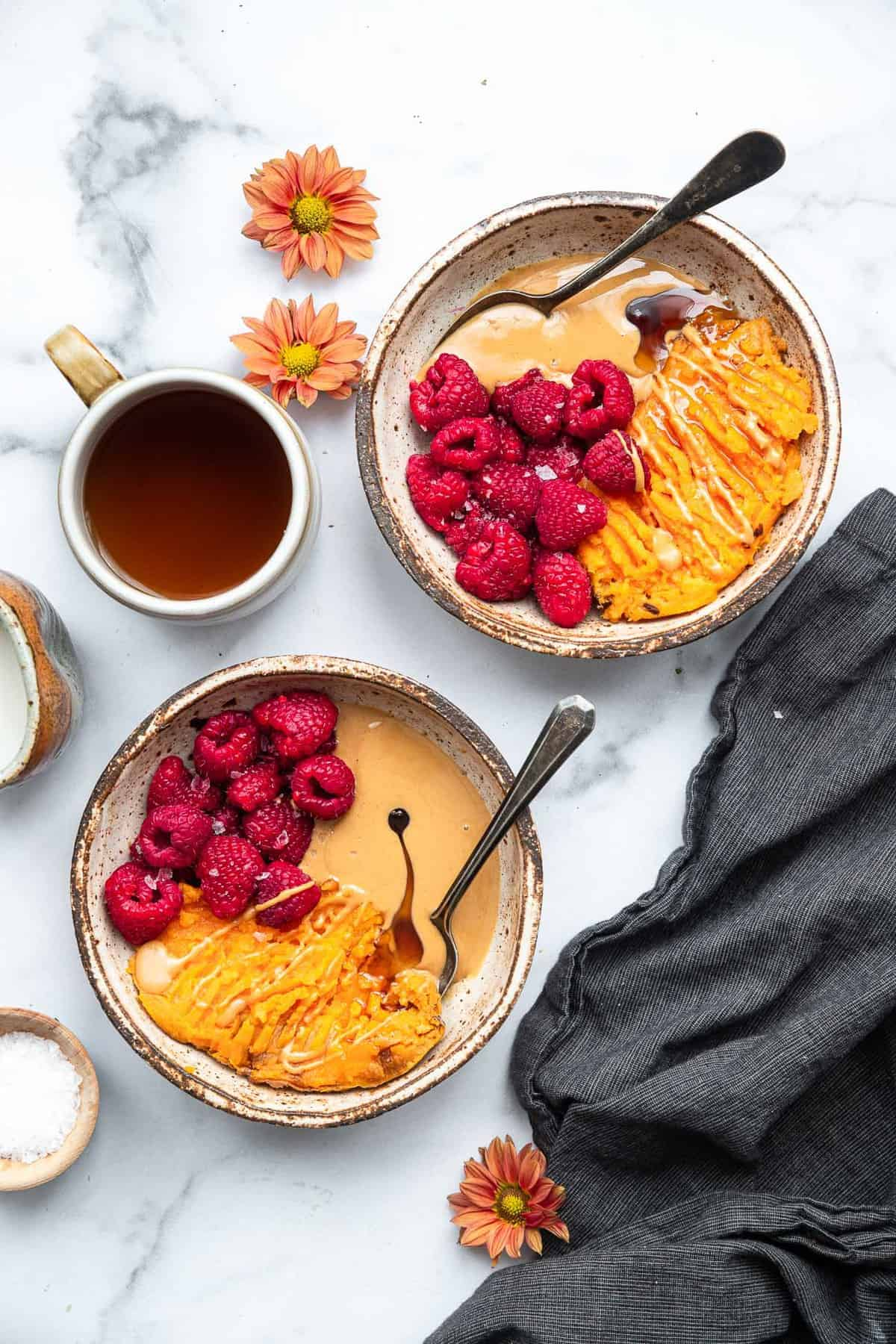 two sweet potato breakfast bowls on the counter with coffee on the side