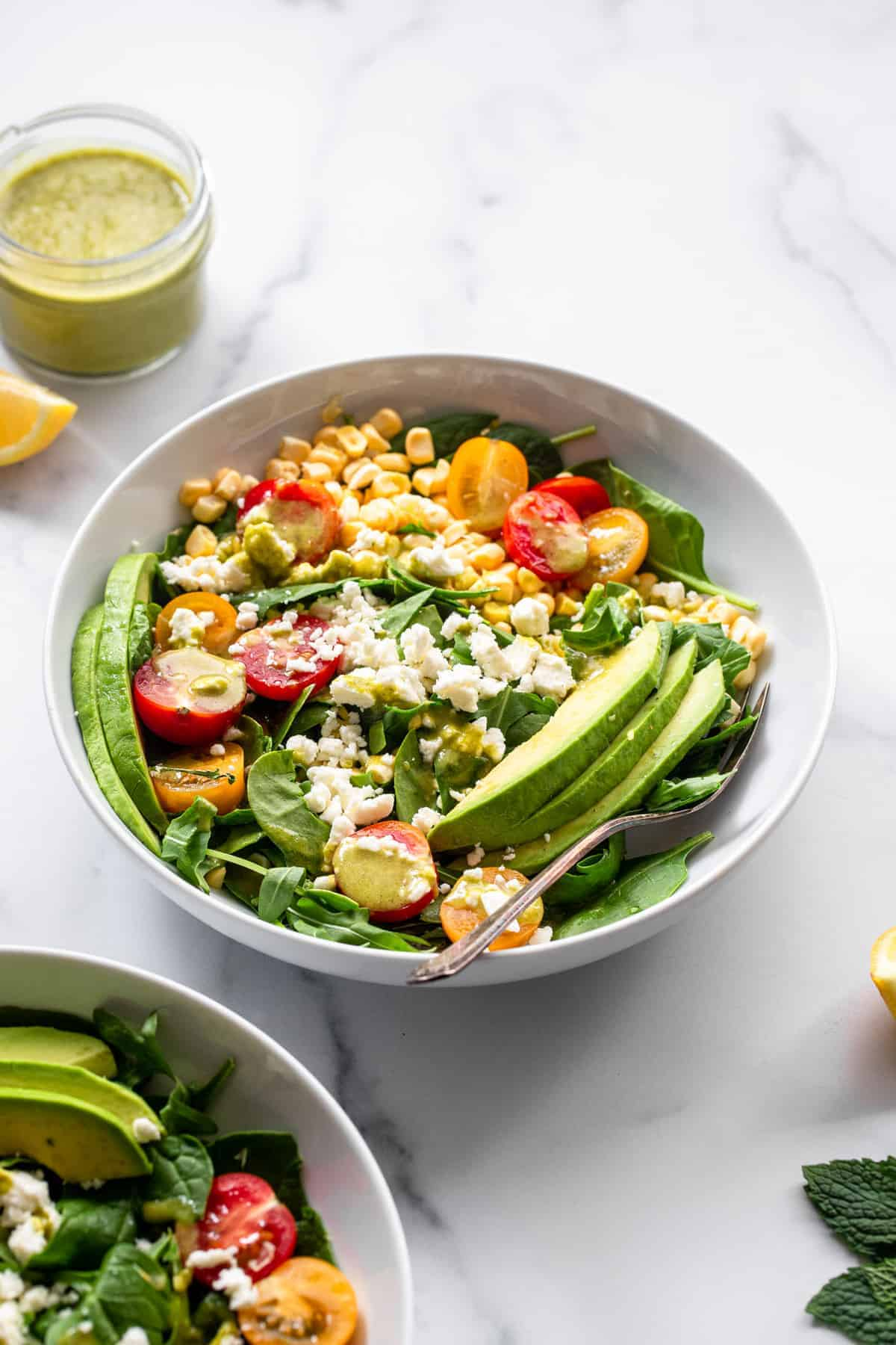 corn feta salad in a bowl with avocado toppings