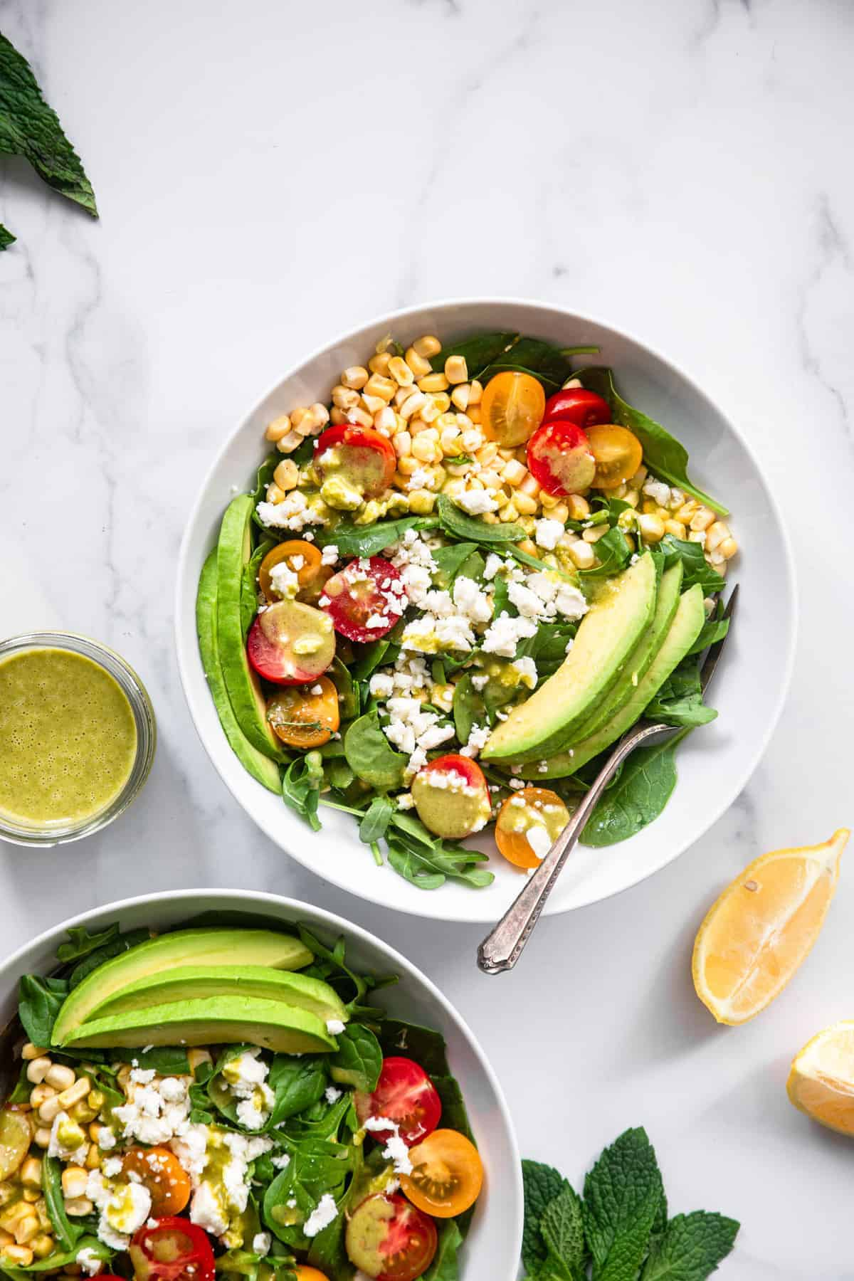 top view of corn feta salad in a bowl with spoon and sauce on the side