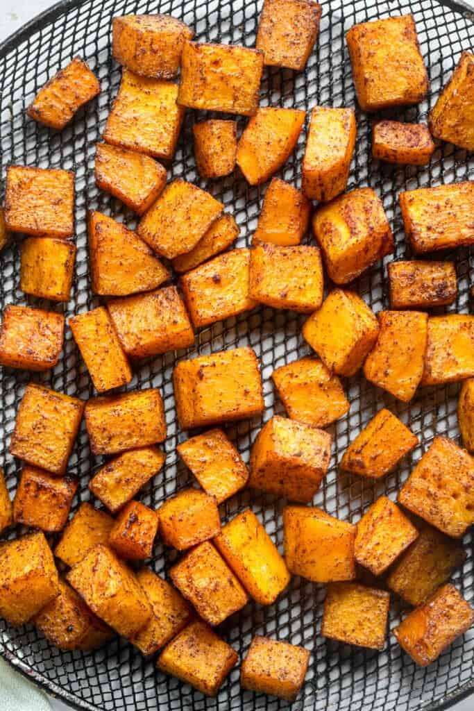 air fryer butternut squash cut into cibes and arranged on a mesh sheet