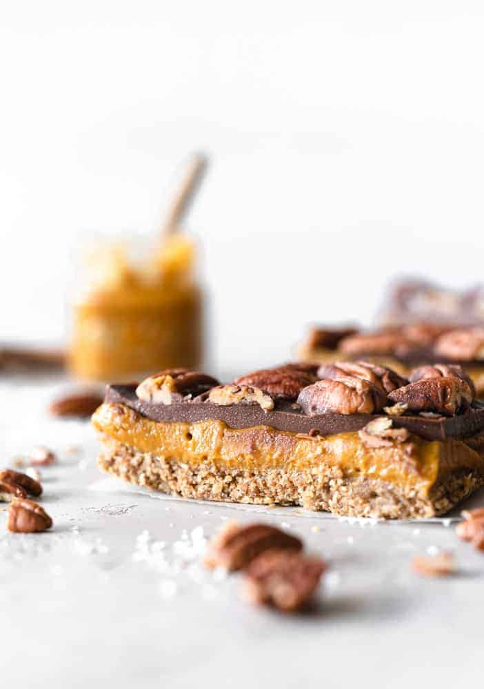 pumpkin pie spice behind a pumpkin spice caramel slice on a table with nuts around it