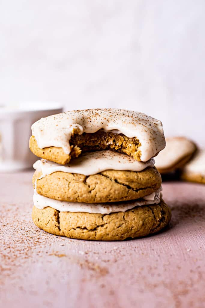 stack of 3 pumpkin sugar cookies with bourbon cinnamon frosting on a table