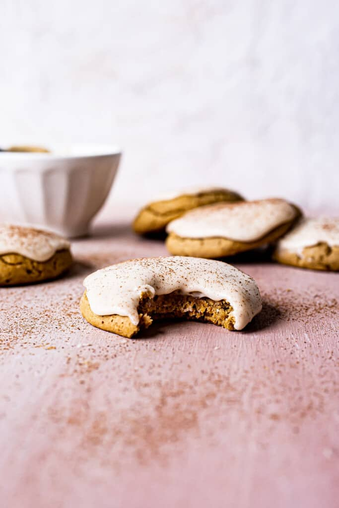 pumpkin sugar cookies with bourbon cinnamon frosting with a bite taken out of it