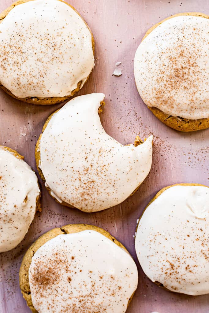 a collage of pumpkin sugar cookies with bourbon cinnamon frosting around on a table