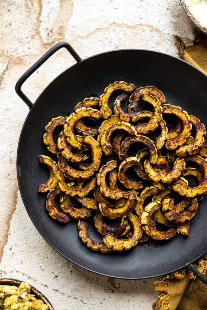 roasted delicata squash in a fry pan on a table