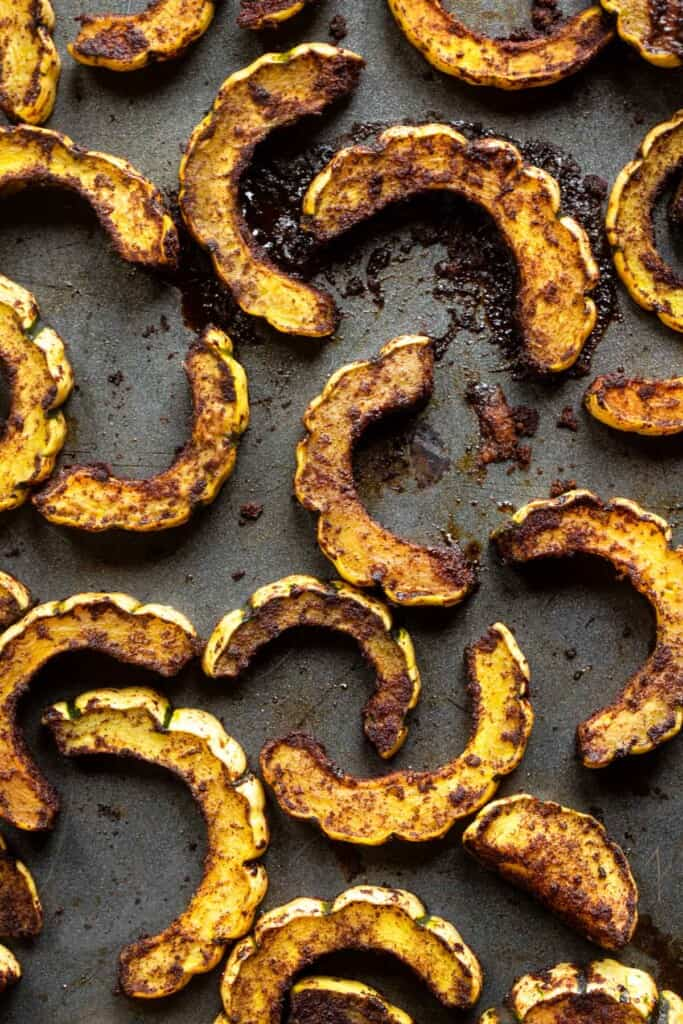 roasted delicata squash spread out on a backing sheet