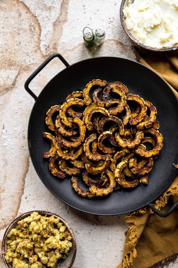 roasted delicata squash in a frying pan with toppings on the side