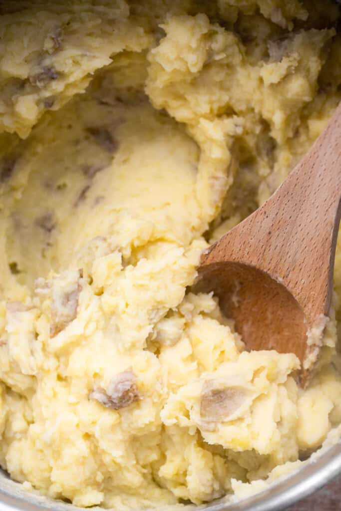 extreme close up of Whole30 Mashed Potatoes being stirred with a wooden spoon
