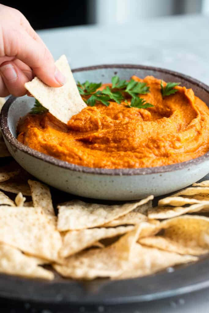 curry sweet potato almond butter dip with a chip being dipped into it