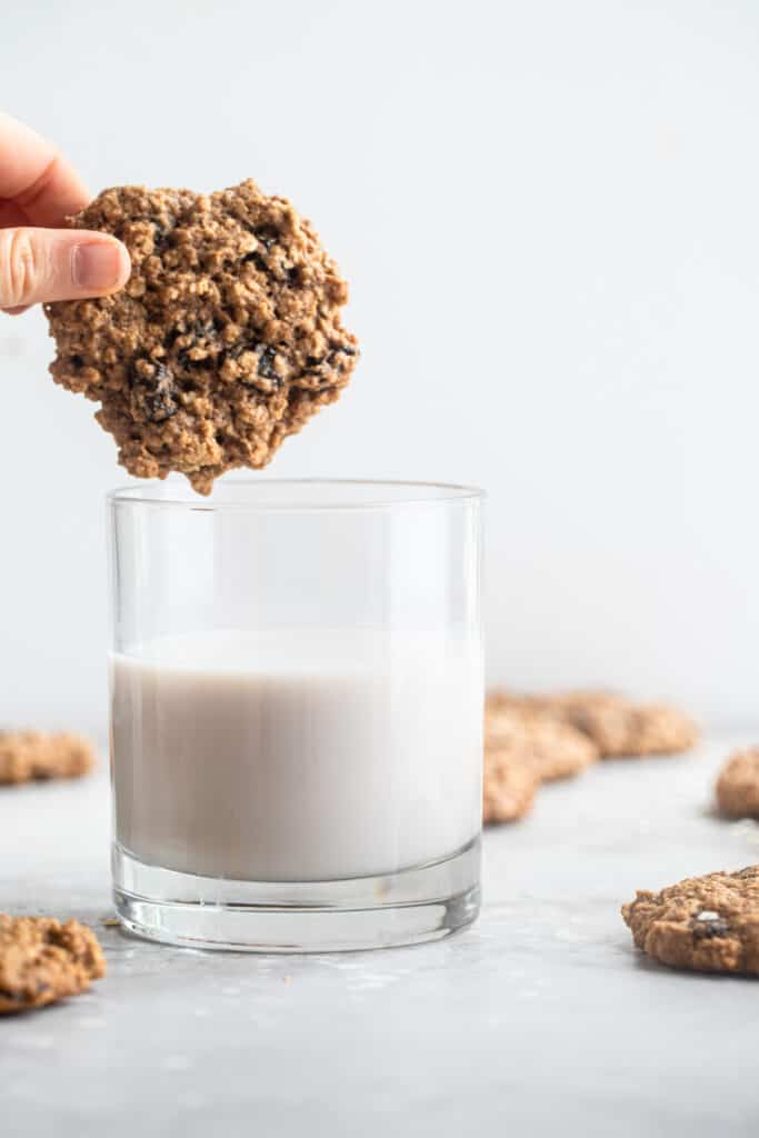 one Healthy Oatmeal Cookies being dipped into a glass of milk