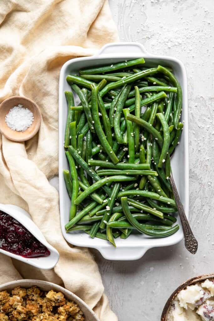 Instant Pot Green Beans in a serving dish on a table with spoon