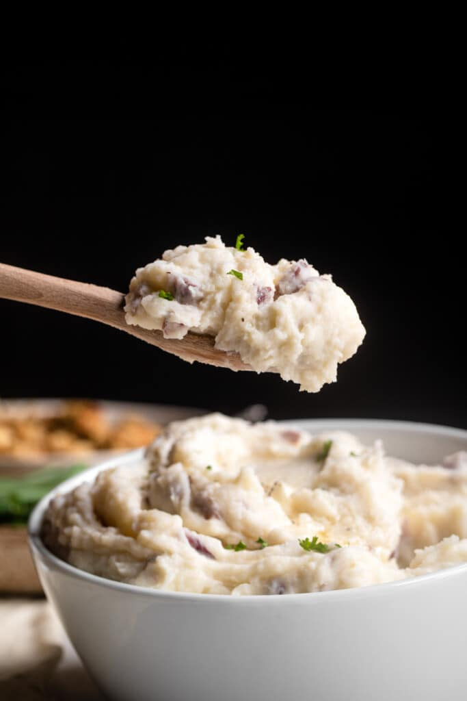 red skin mashed potatoes being scooped out of a bowl with a wooden spoon