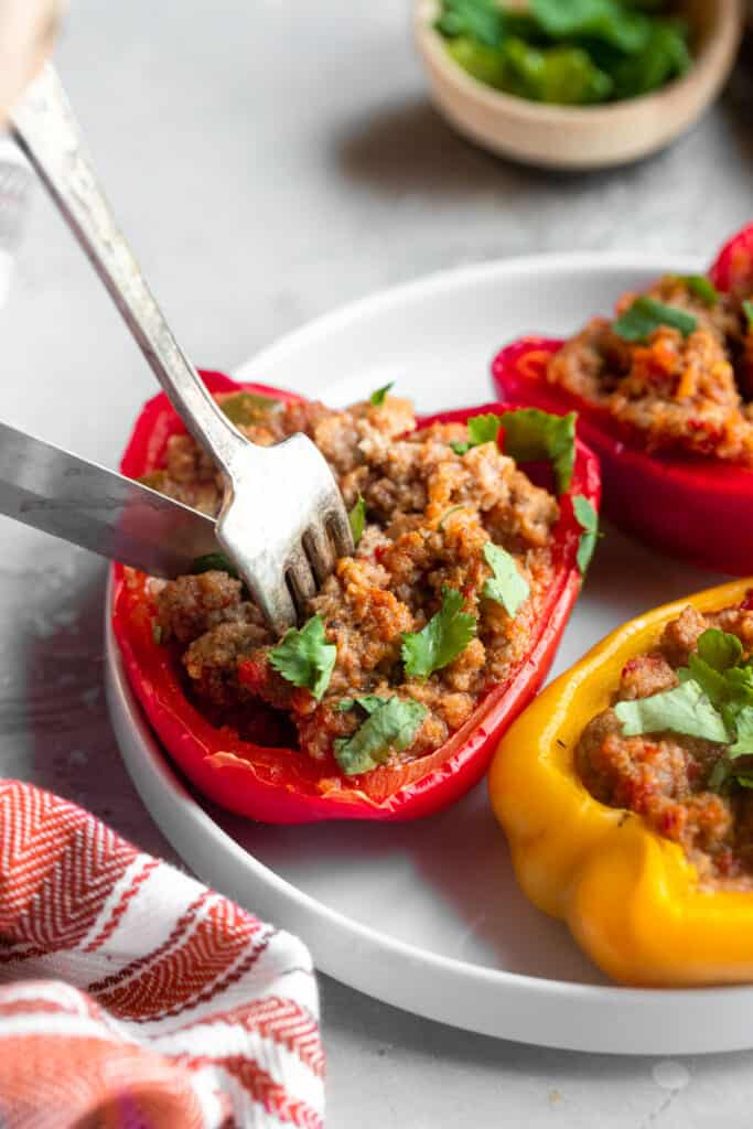a Whole30 Stuffed Pepper on a plate being eaten
