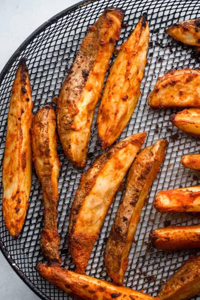 Air Fryer Potato Wedges arranged on a air fryer basket