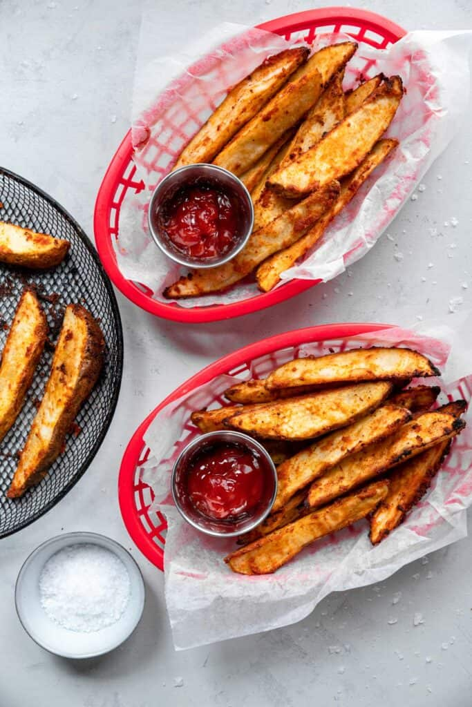 two baskets of Air Fryer Potato Wedges with Ketchup on the side