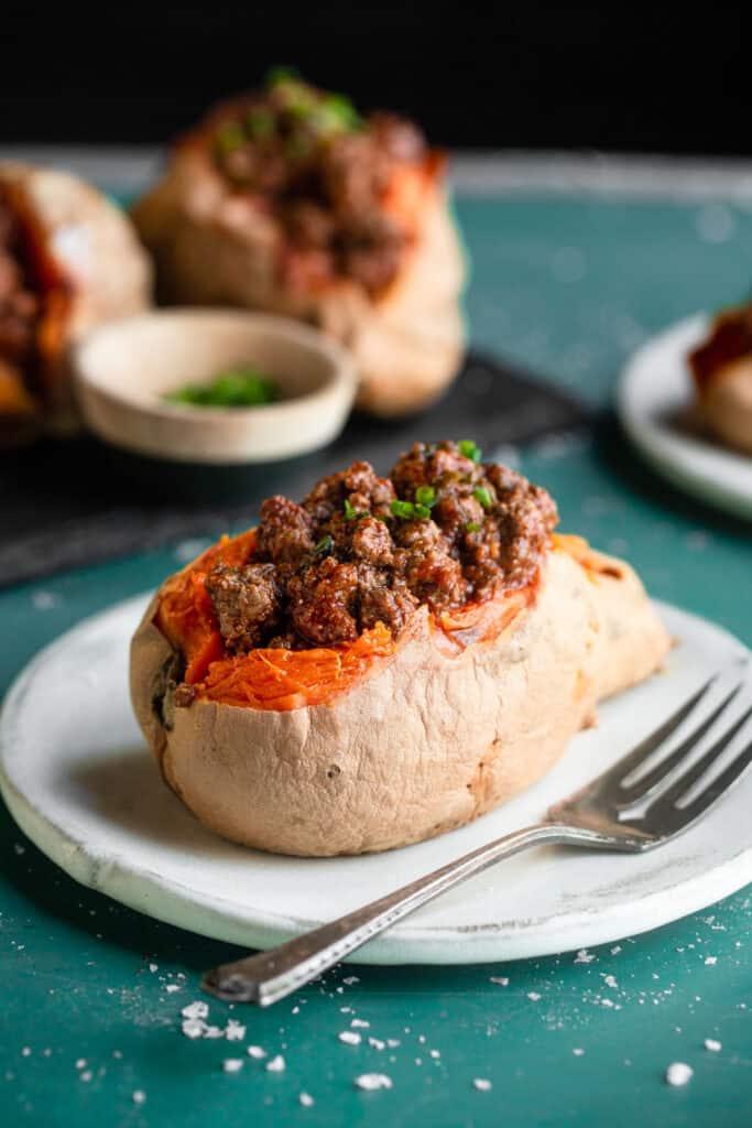 Whole30 Sloppy Joes stuffed into a sweet potato on a plate