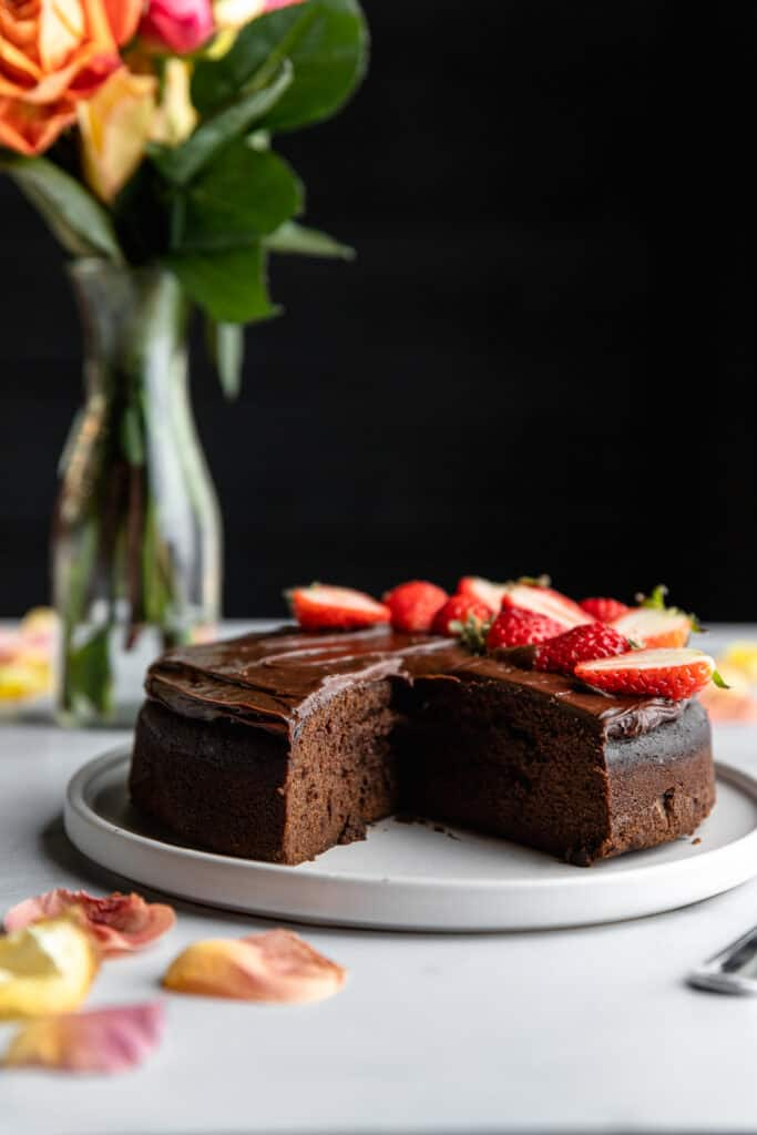 Instant Pot Chocolate Cake on a round plate with a slice cut out