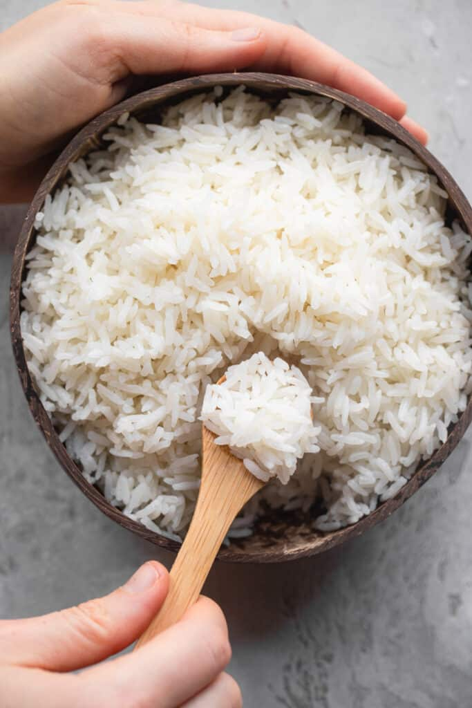 Instant Pot Coconut Rice being scooped out of a wooden bowl
