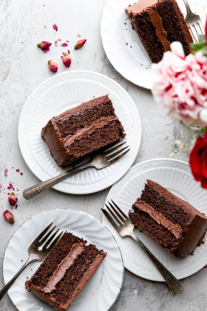 several slices of Keto Chocolate Cake on small plates with forks
