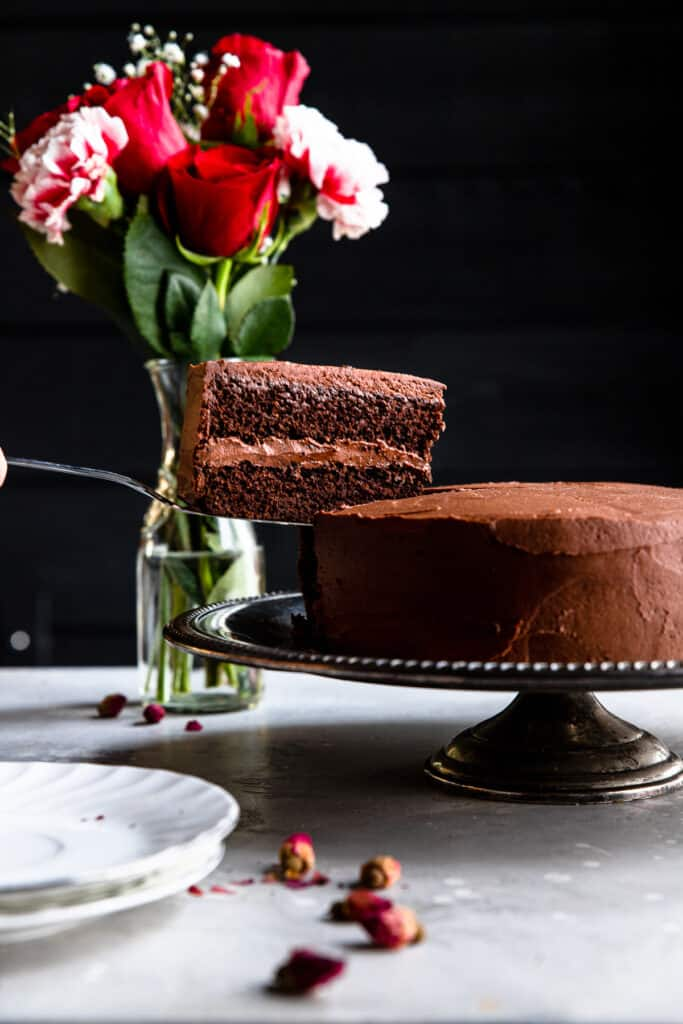 Keto Chocolate Cake on a cake stand with flowers