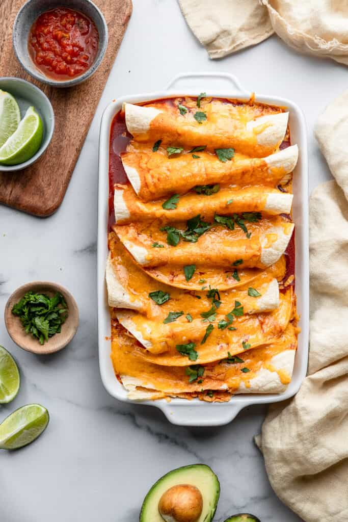 Instant Pot Chicken Enchilada in a dish on a table with toppings on the side