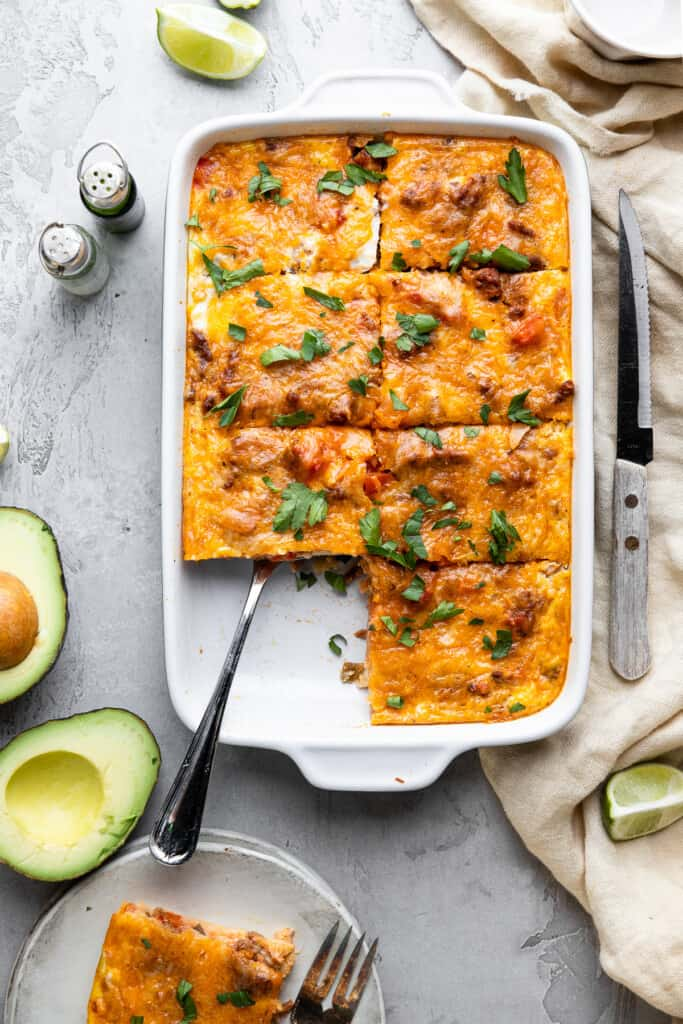 a pan of Mexican Breakfast Casserole with avocado on the side
