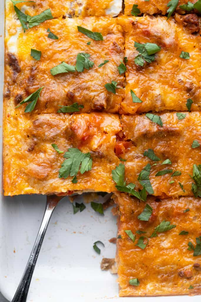 a dish of Mexican Breakfast Casserole with a serving spoon