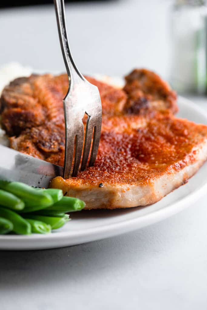 a plat with Air Fryer Pork Chops and green beans