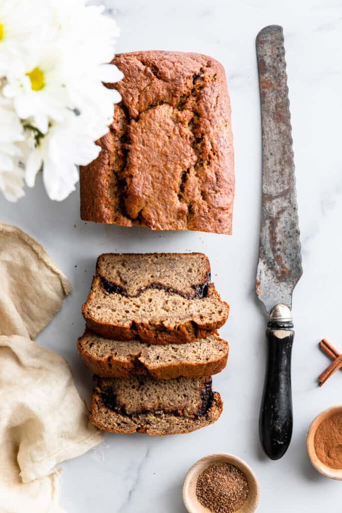 a loaf of Cinnamon Banana Bread with a bread knife next to it