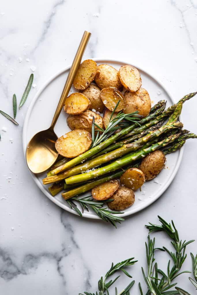 a plate with Roasted Potatoes and Asparagus and a spoon