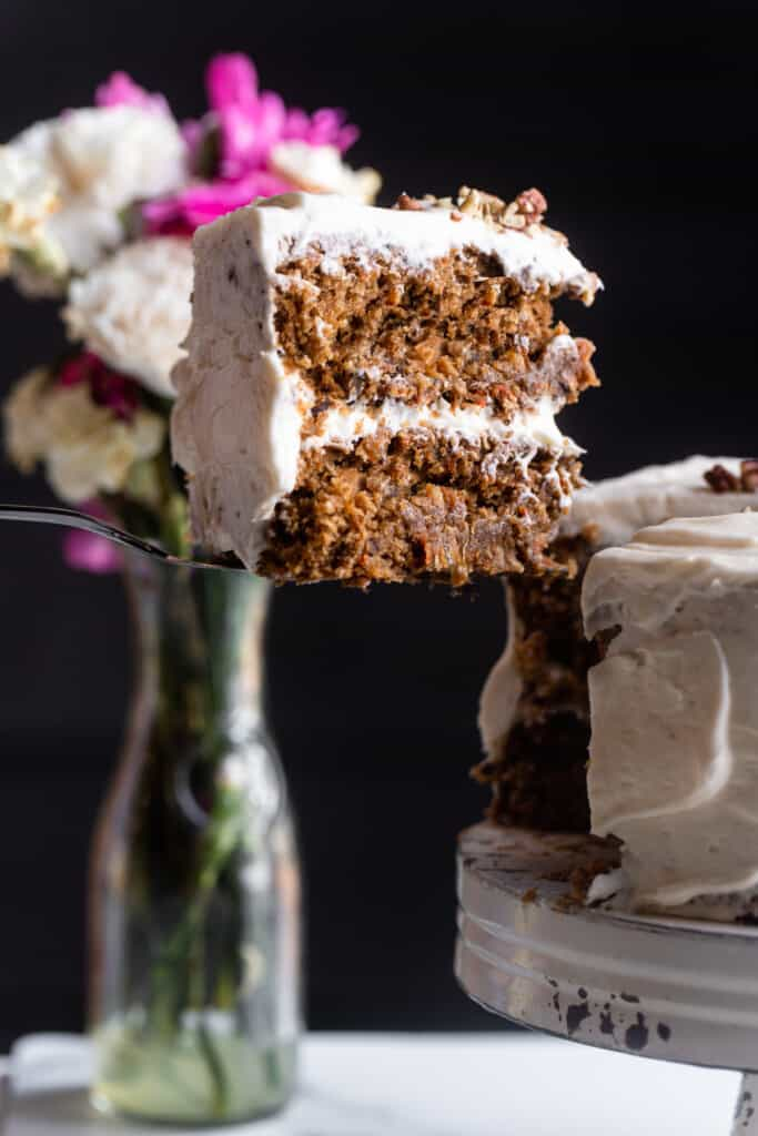 Vegan Carrot Cake on a cake stand with a slice cut out
