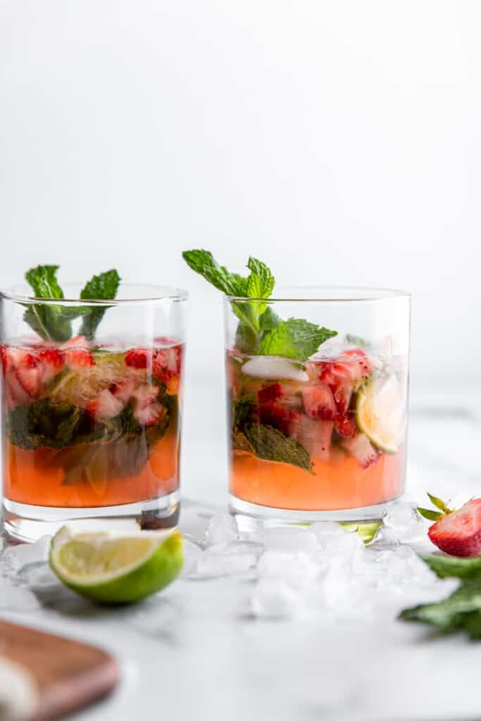 two Strawberry Mojito on a table with mint leaves
