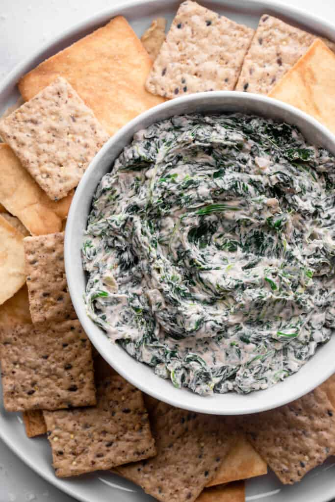 Vegan Spinach Dip in a bowl with crackers on the side