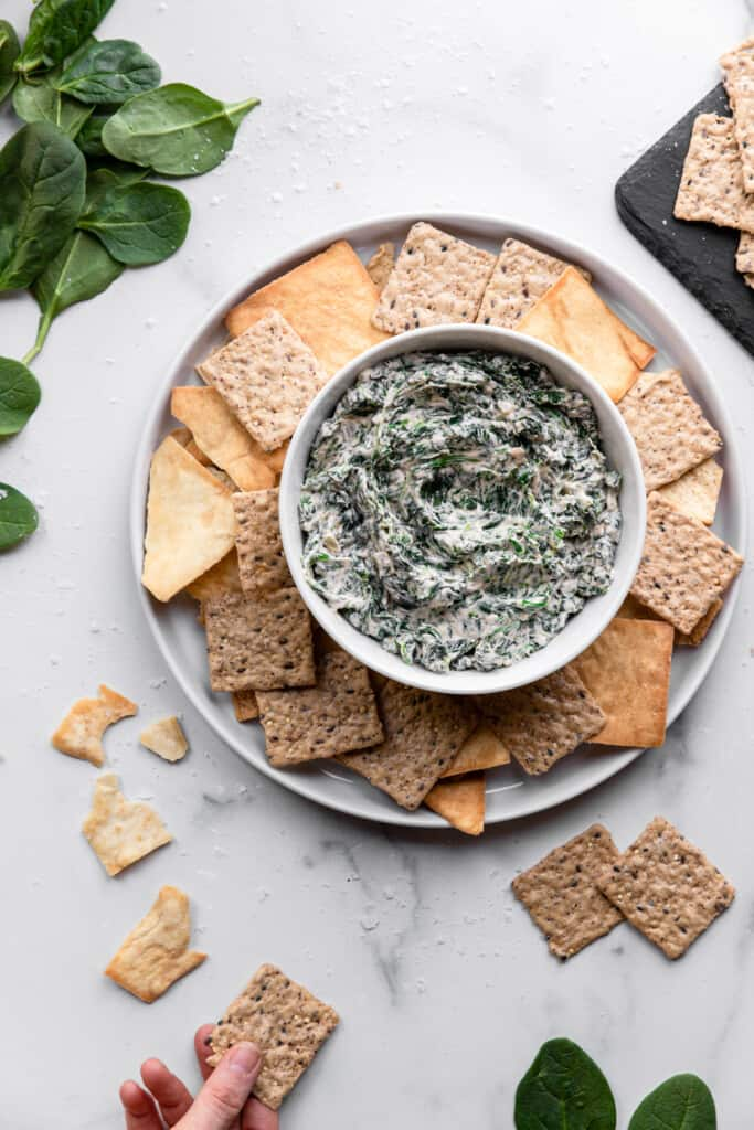 crackers and Vegan Spinach Dip arranged on serving dished