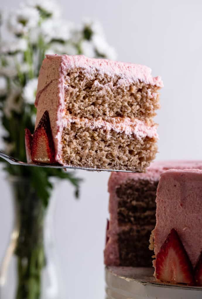 a slice of Vegan Strawberry Cake being cut out of a cake