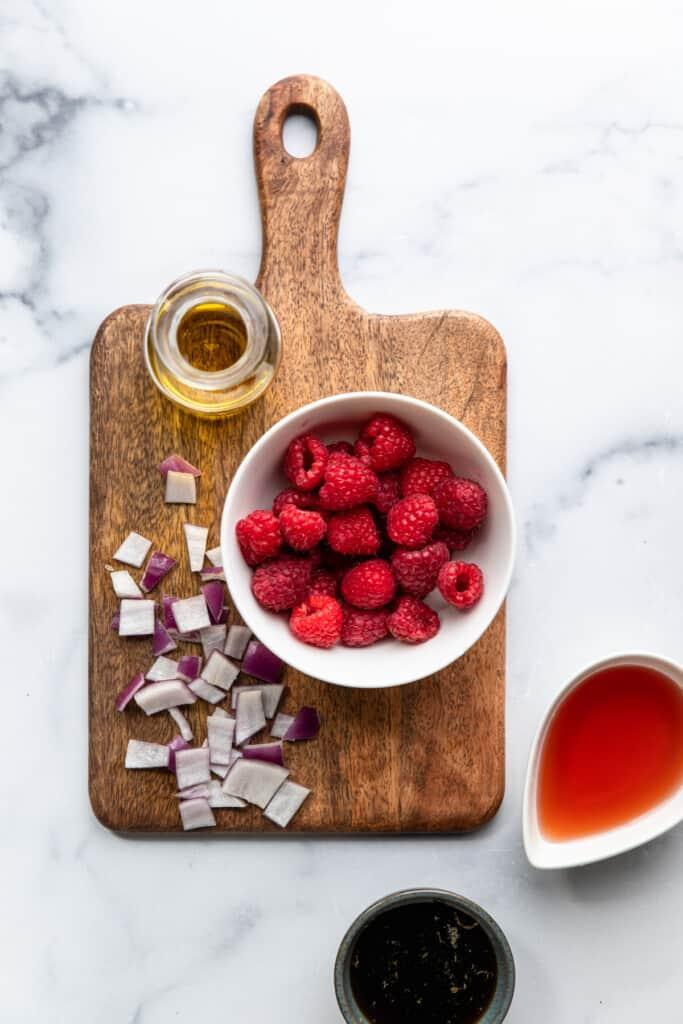 ingredients for Raspberry Vinaigrette on a board