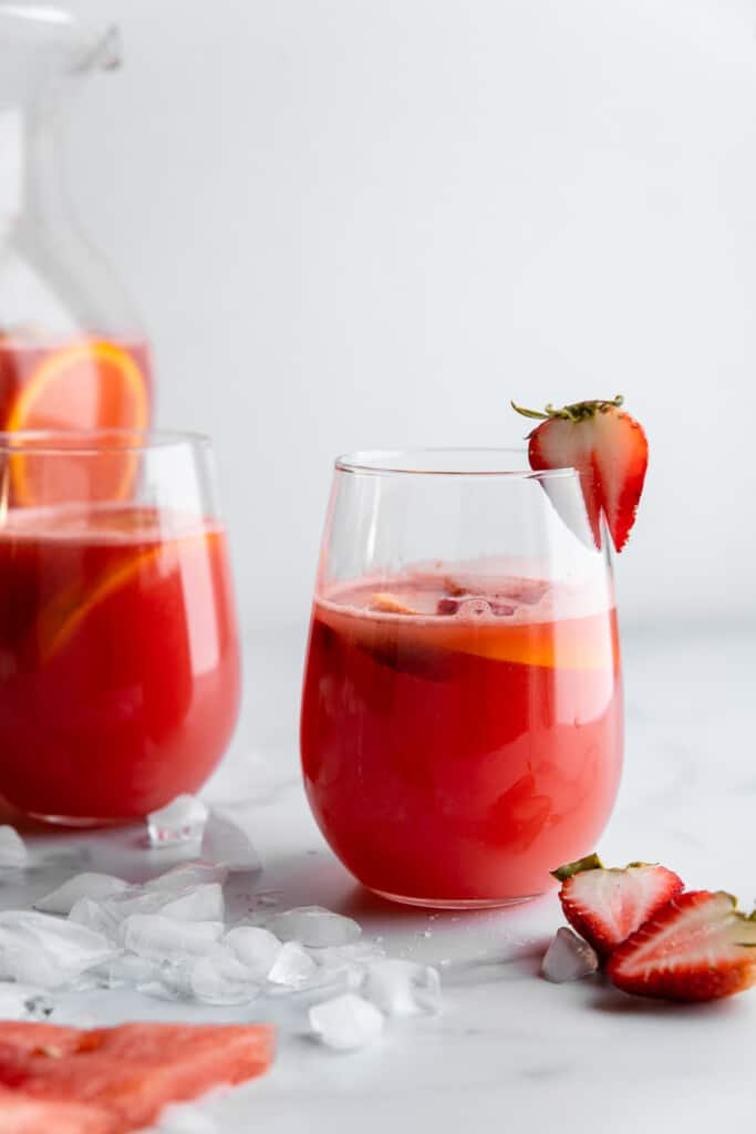 two glasses of Watermelon Sangria with strawberries on the side