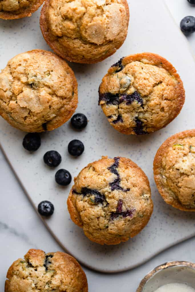 a bunch of Zucchini Blueberry Muffins on a serving board