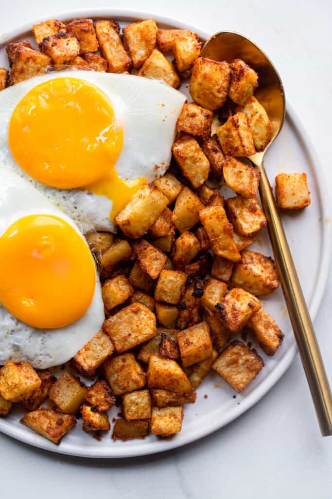 Air Fryer Breakfast Potatoes with eggs and a spoon