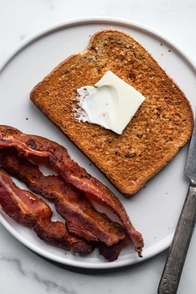 Air Fryer Toast with butter on top and bacon on the side