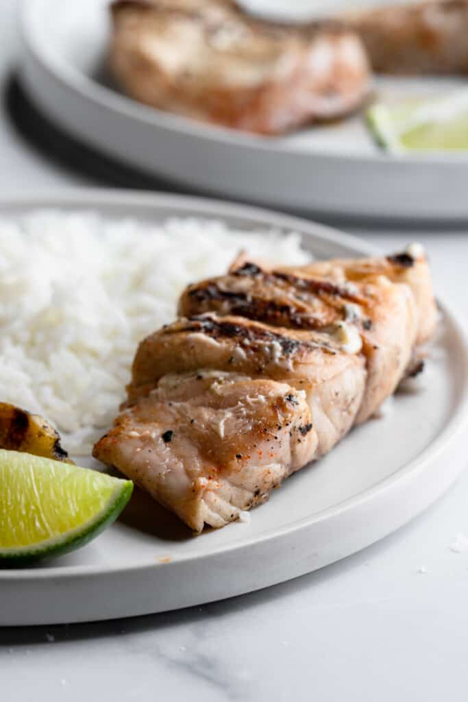 one Grilled Grouper fillet on a dinner plate with rice and lime