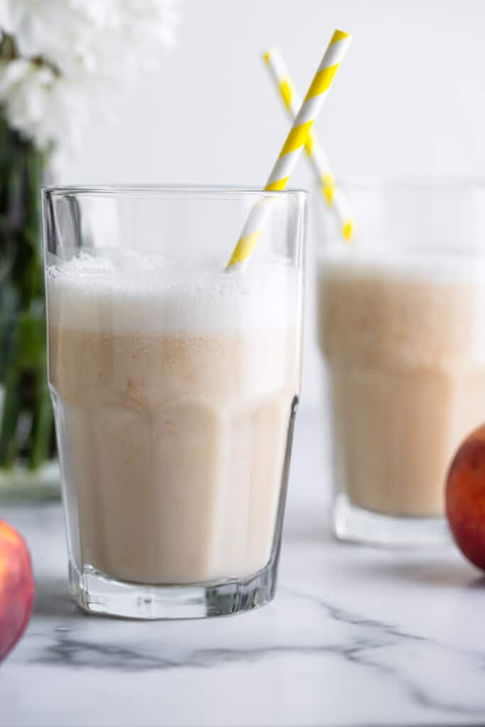 two glasses of Peach Milk with straws