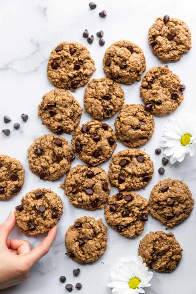 a large batch of Vegan Oatmeal Chocolate Chip Cookies on a table