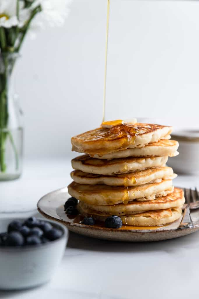 a stack of Dairy Free Pancakes with syrup being poured over